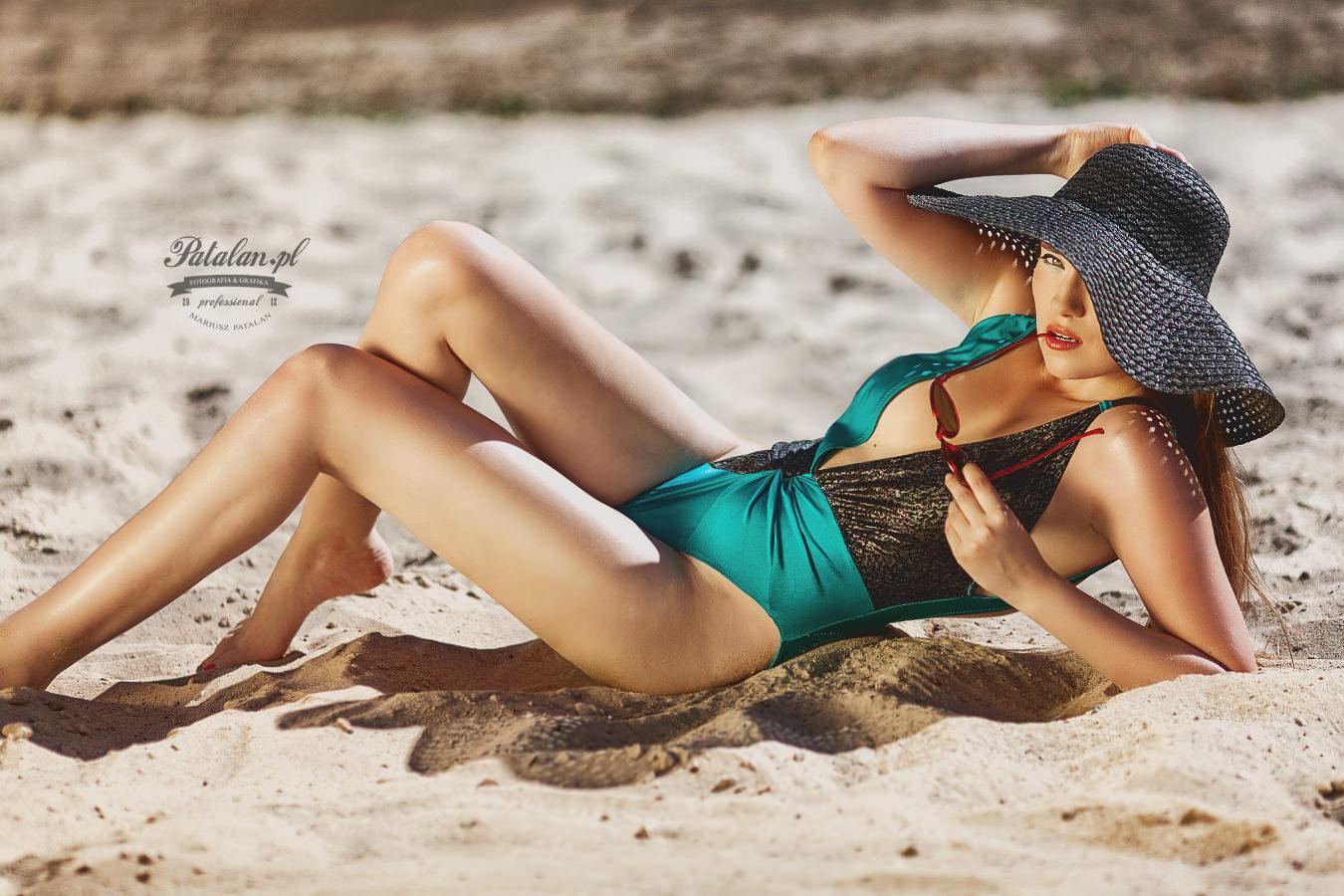 modelka w kapeluszu, strój kąpielowy z lat 20, modelka na plaży, oświetlenie w plenerze, strój kąpielowy,   seksowna modelka na plaży, złota blenda na sesji zdjęciowej, zdjęcia na piasku modelka, strój kąpielowy   modelka